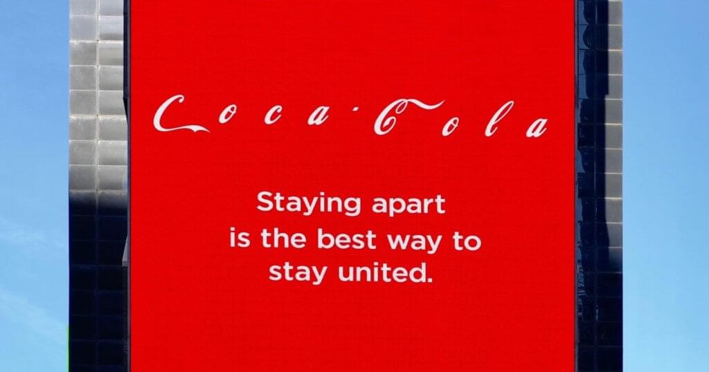 """An image of a Coca-Cola ad on a building. The ad reads """"staying apart is the best way to stay united."""""""
