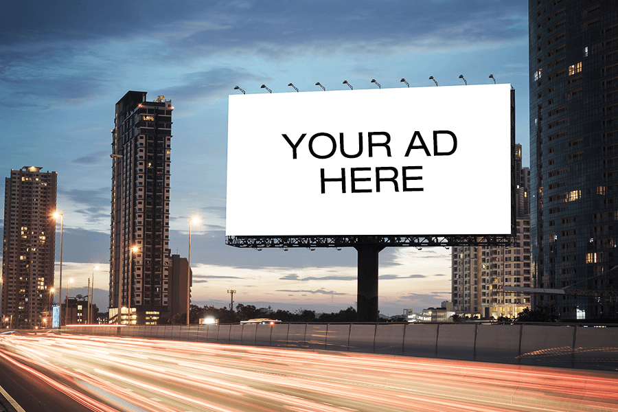 """City landscape with empty billboard along highway that says """"your ad here."""""""