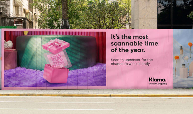 An image of an ad for Klarna on a billboard. The billboard is pink and has an image of a present that's opened and inside is a QR code.