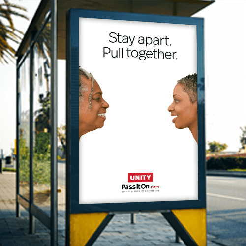 An image of a bus-stop billboard by PassItOn.com. The ad has two women's facing each other and smiling from a distance with a white background.