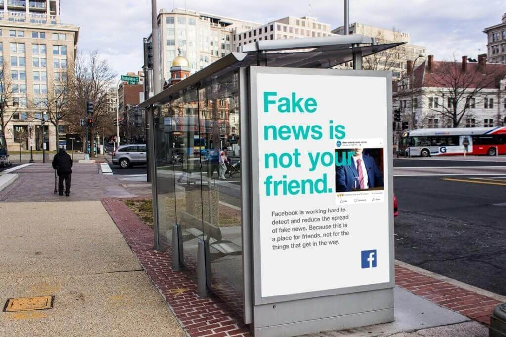 """Facebook bus shelter ad reads """"Fake news is not your friend""""."""