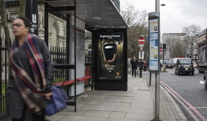 A street corner with a DOOH bus-stop ad for Guinness. The ad displays a mouth thats screaming and tells passersby where they can watch the Six Nations Championship.