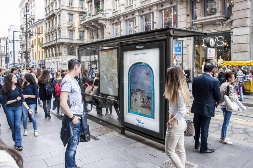 Picture of millennials stopping in their commute to look at a bus shelter advertisement.